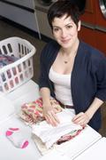 housewife folding laundry at landromat - stock photo