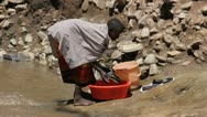 Traditional Maasai Girl Does Laundry in African Stream    (HD) Stock Footage