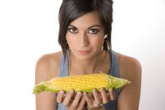 beautiful brunette holds a corn stalk - stock photo