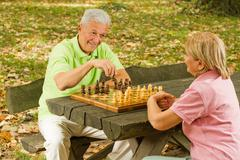 happy senior couple playing chess  - stock photo