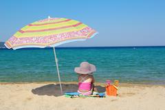 little girl sitting on beach under sunshade.JPG - stock photo