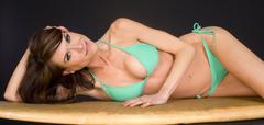 on her board feaml in teal bikini - stock photo