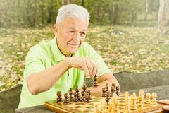 Elderly man playing chess in the park Stock Photos