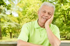 Portrait of smiling old man in the park Stock Photos