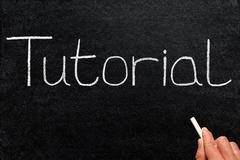 Tutorial written with white chalk on a blackboard. Stock Photos