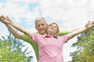 Happy elderly couple with raised arms  Stock Photos