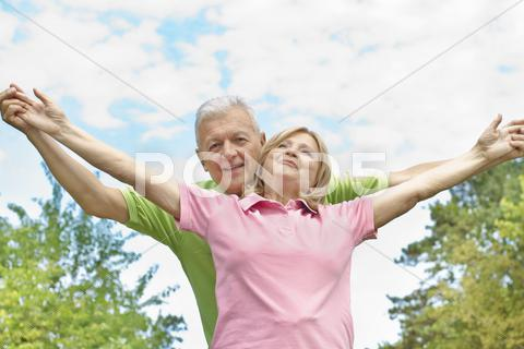 Stock photo of happy elderly couple with raised arms
