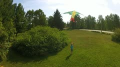 Boy flies his kite in a park Stock Footage