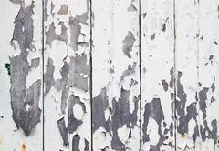 White flaky paint on a old weathered wooden fence. Stock Photos