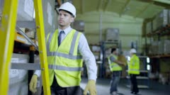Worker in a warehouse climbs a ladder to check stock on a shelf Stock Footage