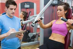 Stock Photo of Trainer taking notes on client on weights machine