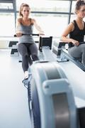 Woman using rowing machine Stock Photos