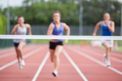 Athletes racing towards finish line - stock photo