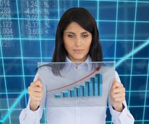 Woman holding hologram of graph - stock photo