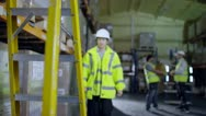 Stock Video Footage of Worker in a warehouse climbs a ladder to check stock on a shelf