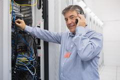 Stock Photo of Man fixing server wires and talking on phone