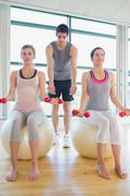 Two women at the gym with their coach - stock photo