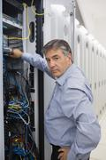 Technician looking up from adjusting server wires Stock Photos