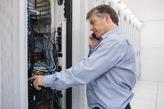 Technician phoning while repairing a server - stock photo