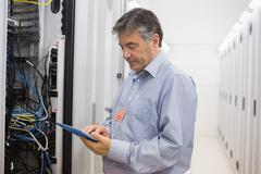 Stock Photo of Technician checking the server with tablet pc