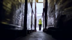 Stock Video Footage of A male industrial worker walks in between rows of goods in a warehouse