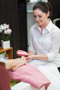 Woman buffering toe nails at spa center Stock Photos