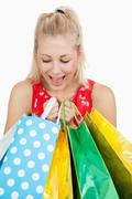 Stock Photo of Cute excited woman looking into her shopping bags
