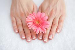 Flower on french manicured fingers at spa center - stock photo