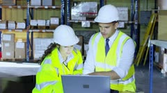 Male and female warehouse workers discuss the logistics of their business Stock Footage