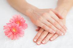 Flowers with french manicured fingers - stock photo