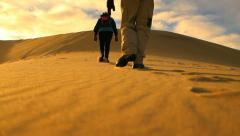 Death Valley Hikers Walk Up Huge Sand Dune Mountain in Desert Sun Stock Footage