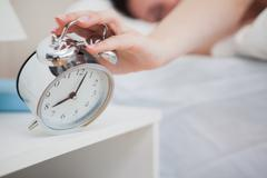 Woman in bed extending hand to alarm clock - stock photo