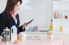 Business woman text messaging while having breakfast in kitchen Stock Photos