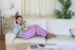 Bored woman having popcorn on couch at home - stock photo