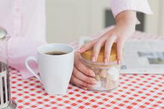 Woman with coffee cup and container of sugar cubes - stock photo