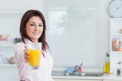 Stock Photo of Portrait of woman offering you orange juice