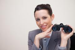 Portrait of business woman with binoculars smiling - stock photo