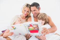 Happy family reading a story together Stock Photos