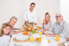 Smiling father cutting slices of turkey - stock photo