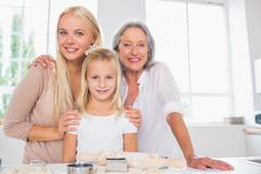 Stock Photo of Cheerful mothers and daughters cooking together