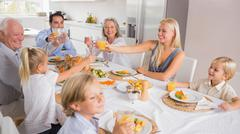 Happy family raising their glasses - stock photo