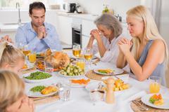 Family praying before dinner - stock photo