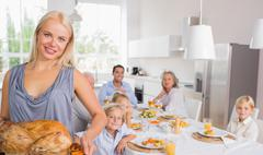 Blonde woman showing the roast turkey - stock photo