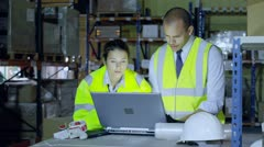 Warehouse workers are discussing their business and looking at a laptop computer - stock footage