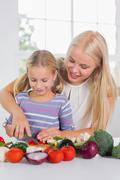 Stock Photo of Focused mother teaching cutting vegetables