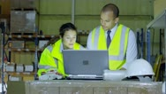Stock Video Footage of 2 warehouse workers in high visibility clothing discuss their business