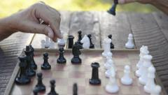 Active retired people, two senior men playing chess at park Stock Footage