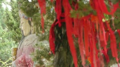 Red ribbon wrapped around branches.China Fortuna sculpture in temple.historical Stock Footage