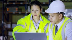Male and female warehouse managers discussing their business - stock footage