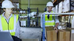 2 warehouse employees discuss stock and storage requirements - stock footage
